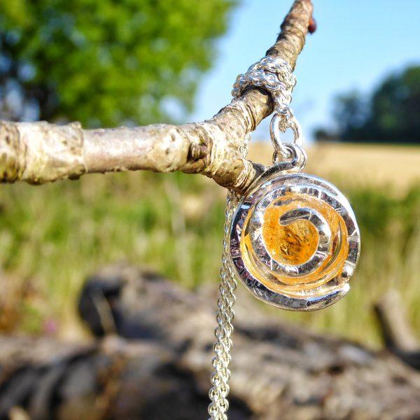 Golden citrine set within a textured silver spiral.